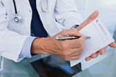 Close up of a male doctor showing a blank prescription sheet — Stock Photo