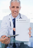Portrait of a doctor showing a blank prescription sheet — Stock Photo
