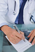 Portrait of a doctor writing a prescription — Stock Photo