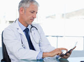 Serious doctor working with a tablet computer — Stock Photo