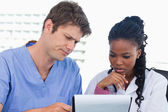 Doctors looking at a document — Stockfoto