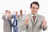 Salesman with team behind him giving thumbs up — Stock Photo