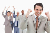 Smiling businessman with team behind him raising fists — Stock Photo