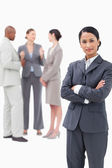 Saleswoman with negotiating trading partners behind her — Stock Photo