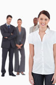 Smiling businesswoman with three co-workers behind her — Stock Photo