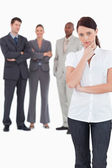 Thinking businesswoman with three colleagues behind her — Stock Photo