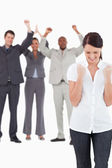 Triumphant businesswoman with cheering colleagues behind her — Stock Photo