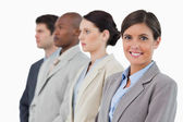 Smiling saleswoman standing next to her associates — Stock Photo