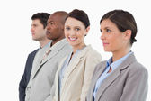 Smiling saleswoman standing between her associates — Stock Photo