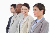 Smiling saleswoman standing between her associates — Stock Photo