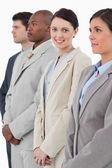 Smiling businesswoman standing between her associates — Stock Photo