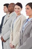 Smiling businesswoman standing between her associates — Stock Photo