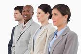 Smiling salesman standing between his associates — Stock Photo