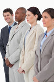 Smiling salesman standing next to his associates — Stock Photo