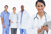 Smiling doctor with clipboard and members of staff behind her — Stock Photo