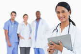 Female doctor with clipboard and staff members behind her — Foto Stock