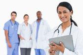 Médica com área de transferência e membros da equipe atrás dela — Foto Stock