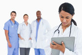 Female doctor taking notes on clipboard with staff members behin — Stock Photo