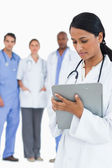 Female doctor reading notes with staff members behind her — Stock Photo