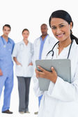 Smiling female doctor with clipboard and staff behind her — Stock Photo