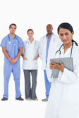 Female doctor with clipboard and colleagues behind her — Stock Photo