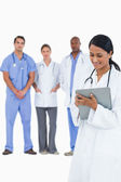 Female doctor taking notes with staff members behind her — Stock Photo