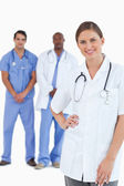 Smiling doctor with male colleagues behind her — Stock Photo