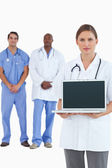 Female doctor showing laptop with colleagues behind her — Stock Photo