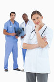 Doctor in thinkers pose with colleagues behind her — Stock Photo