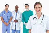 Médica com colegas atrás dela — Foto Stock