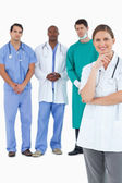 Smiling doctor with male staff members behind her — Stock Photo