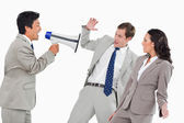 Businessman with megaphone yelling at colleagues — Stock Photo