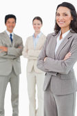 Smiling tradeswoman with folded arms and associates behind her — Stock Photo