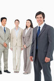 Smiling young salesman with team behind him — Stock Photo