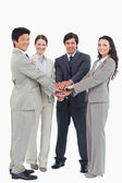 Smiling businessteam putting their hands together — Stock Photo