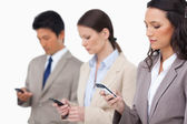 Businessteam looking at their cellphones — Stock Photo