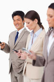 Smiling businessman with cellphone next to colleagues — Stock Photo