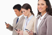 Smiling saleswoman with cellphone next to colleagues — Stock Photo