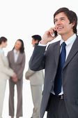 Salesman talking on mobile phone with team behind him — Stock Photo