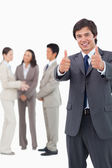 Salesman giving thumbs up with team behind him — Stock Photo