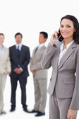 Smiling saleswoman on cellphone with team behind her — Stock Photo