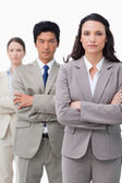 Businesswoman standing with team and folded arms — Stock Photo