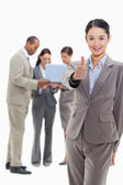Businesswoman smiling and approving with co-workers in the backg — Stock Photo