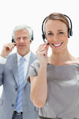 Close-up of a smiling woman wearing a headset with a white hair businessman in background — Stock Photo