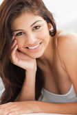 Close up of woman with a hand against her cheek, smiling and loo — Stock Photo