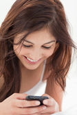 Close up, woman using her smartphone and smiling — Stock Photo
