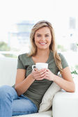 Woman holding a cup, smiling as she looks forward with crossed l — Stockfoto