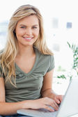 Close up, woman using a laptop while looking forward and smiling — Stock Photo