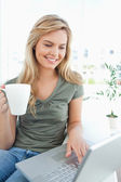 Woman smiling as she uses her laptop and holds a cup in her free — Stock Photo
