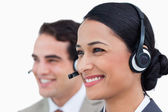 Close up side view of smiling call center agents — Stock Photo
